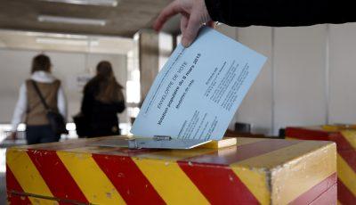 Une citoyenne met son bulletin de vote pour les votations federales et la votation cantonale sur la loi de la police dans l'urne aux couleurs genevoises dans le bureau de vote de Carouge, ce dimanche 8 mars 2015 a Carouge. Les Genevois ont decide dimanche de restructurer de fond en comble l'institution. Ils ont accepte la nouvelle loi sur la police a une tres courte majorite de 50,02 pour cent. L'ecart entre le oui et le non est de 42 voix. (KEYSTONE/Salvatore Di Nolfi)