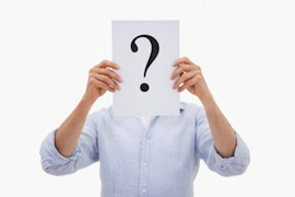Portrait of a man hiding his face behind a question mark