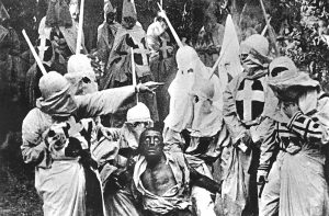 Actors costumed in the full regalia of the Ku Klux Klan chase down a white actor in blackface in a still from 'The Birth of a Nation,' the first feature-length film, directed by D. W. Griffith, California, 1914.