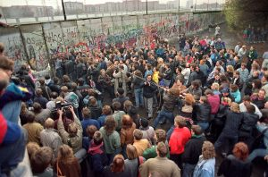 "West Berliners crowd in front of the Berlin Wall early 11 November 1989 as they watch people trying to demolish a section of the wall in order to open a new crossing point between East and West Berlin, near the Potsdamer Square. Two days before, Gunter Schabowski, the East Berlin Communist party boss, declared that starting from midnight, East Germans would be free to leave the country, without permission, at any point along the border, including the crossing-points through the Wall in Berlin. The Berlin concrete wall was built by the East German government in August 1961 to seal off East Berlin from the part of the city occupied by the three main Western powers to prevent mass illegal immigration to the West. According to the ""August 13 Association"" which specialises in the history of the Berlin Wall, at least 938 people - 255 in Berlin alone - died, shot by East German border guards, attempting to flee to West Berlin or West Germany. AFP PHOTO GERARD MALIE"